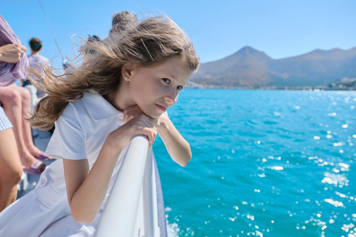 Young girl leaning over railing on a cruise ship