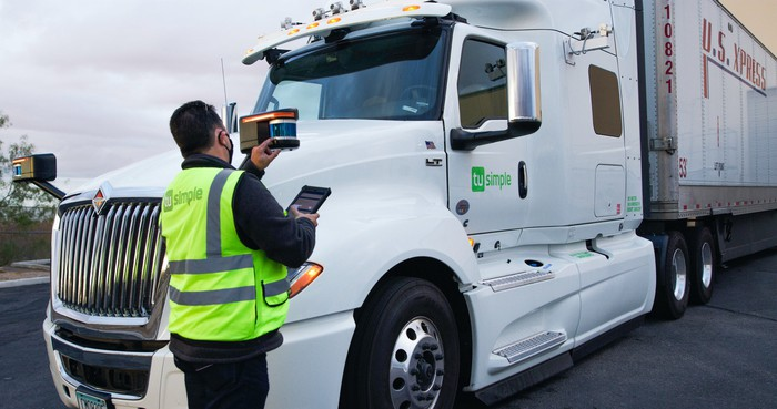 A technician checks a lidar unit on an International semi truck fitted with TuSimple's driverless system.