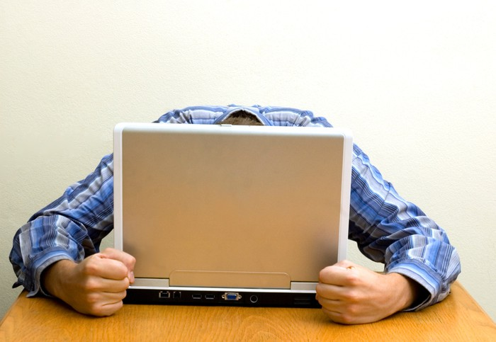 A person sitting at a desk with their head on a laptop computer.