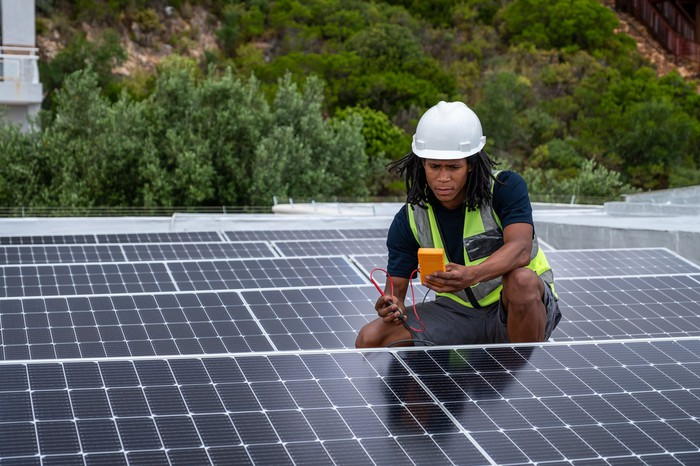 worker checking solar panels with hill of trees in background.