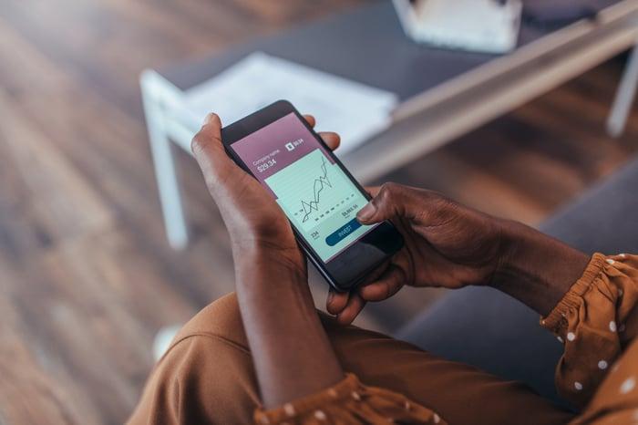 Người cầm điện thoại thông minh có biểu đồ đường và nút đầu tư trên màn hình.