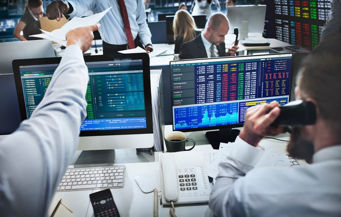 Professional brokers at their desks, with stock quotes and charts displayed on their computers.