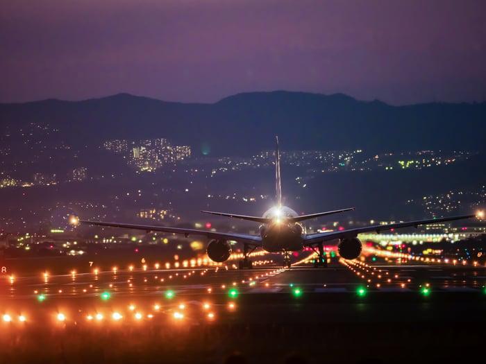 A plane landing on a lit-up tarmac at night.