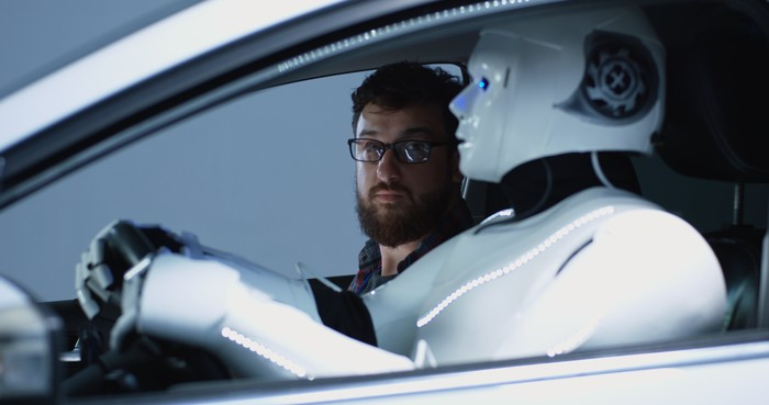 Passenger in car looks skeptically at his robot driver