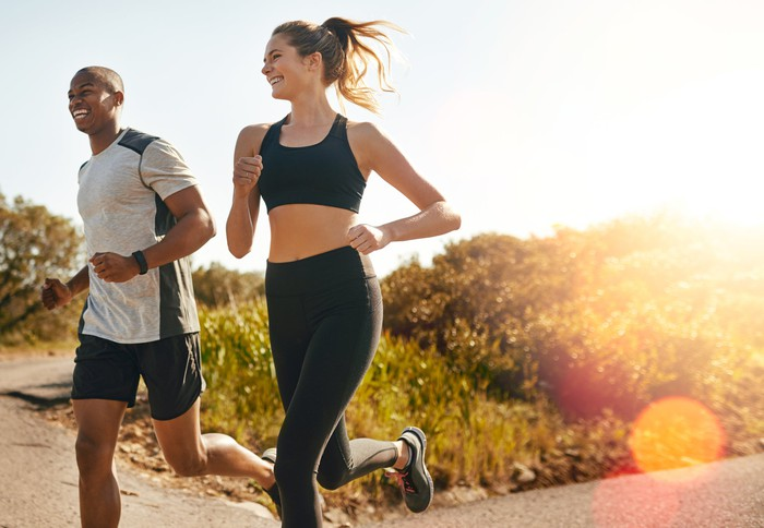 A man and woman smiling while jogging together.