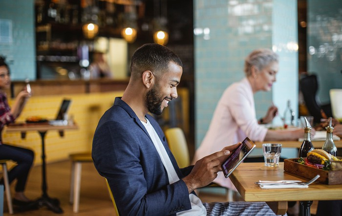 Smiling business person in coffee shop looking at tablet.