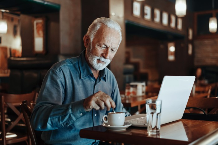 Senior sitting in coffee shop with laptop and cup of coffee.
