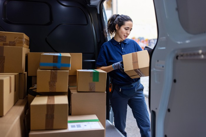 A delivery person standing outside of a delivery van looking at a package.
