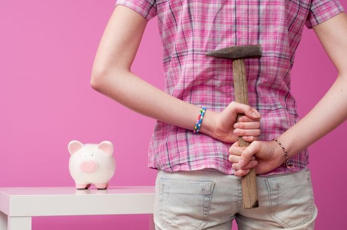 A woman holding a hammer behind her back approaches a piggy bank.