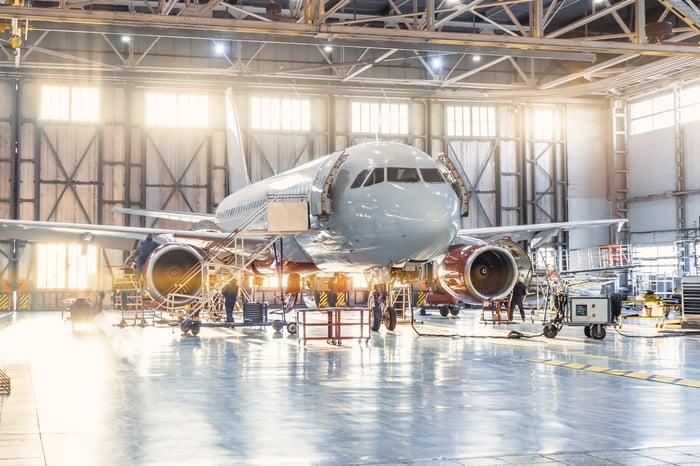 A plane receiving maintenance in a hangar.