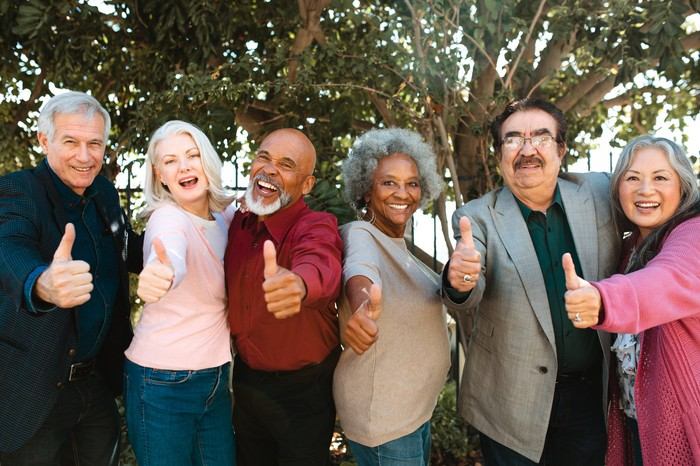 A group of people with their thumbs up.