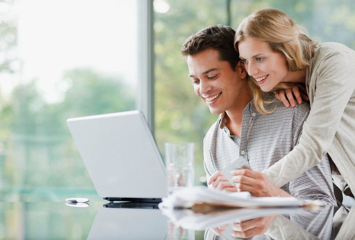 Smiling adult couple looks at laptop together.