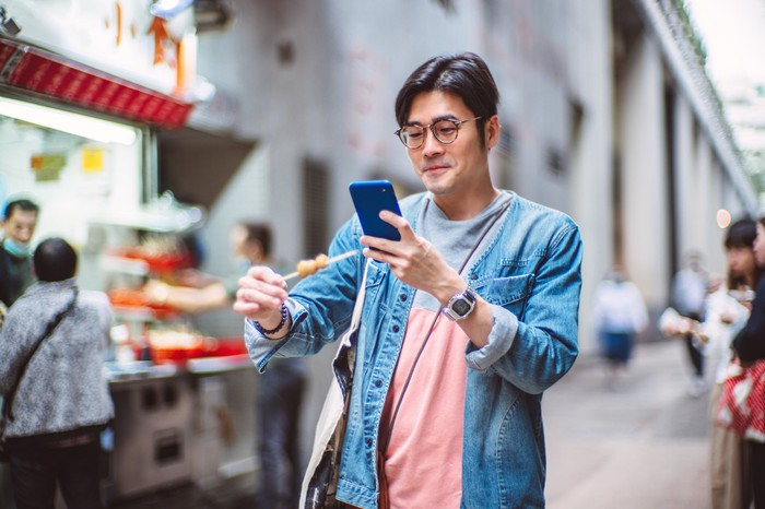 A young man looks at his phone while eating food on a stick walking down the street.