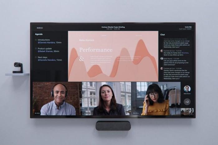 Expositor de pared con tres personas y diapositivas para reuniones.