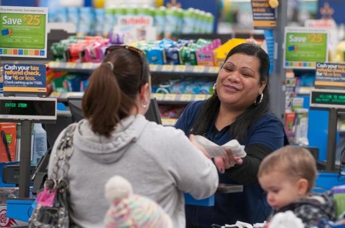 A Walmart cashier handing a receipt to a customer.