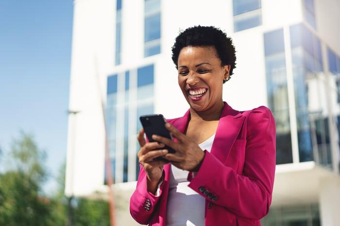 Personne souriante debout devant un immeuble de bureaux alors qu'elle regarde son téléphone.