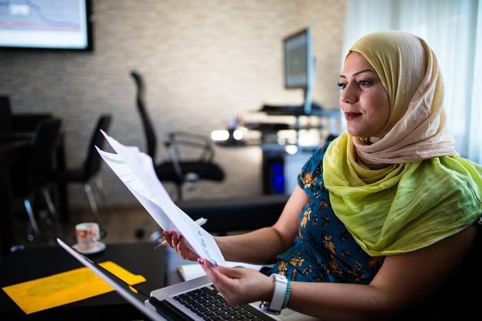 jeune portant un foulard aux couleurs vives examinant des documents financiers