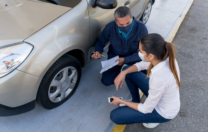 Woman talks to a mechanic about a flat tire on her car.