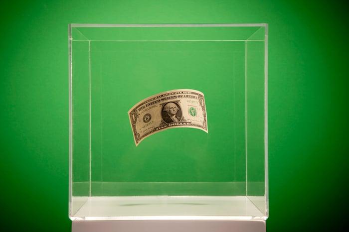A dollar bill in a glass box.