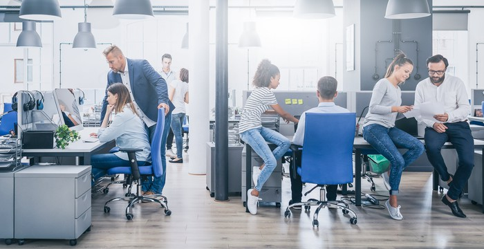 An office with six people in it, working together in pairs
