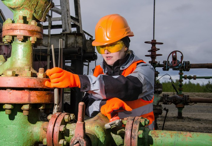 A person in protective gear working on an energy pipeline.