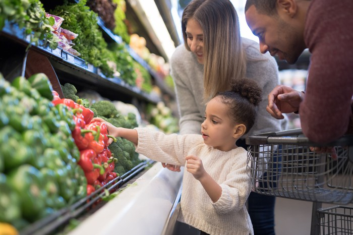 A young child chooses vegetables for his parents at the grocery store.