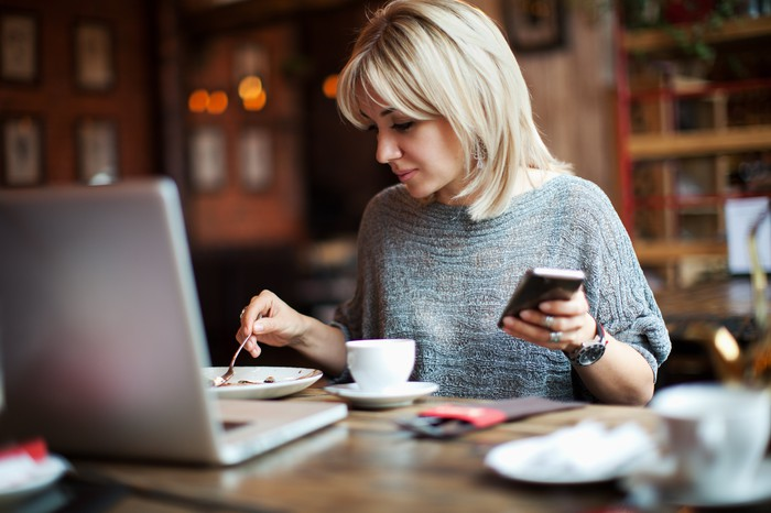 a woman sits at a table in a room holding a cell phone. On the table is a plate, a coffee cup and a laptop.