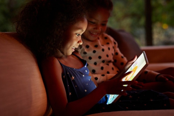 Two children play a game on a tablet.