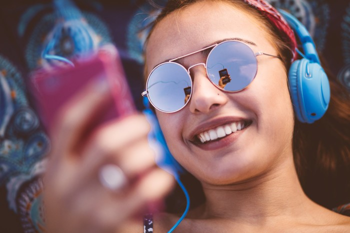 A smiling person wearing sunglasses listens to music on a phone.