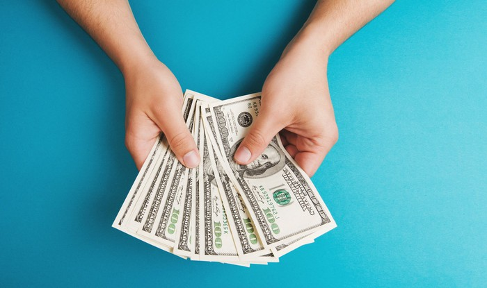 Person holding hundred dollar bills against a blue background