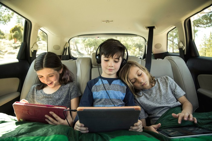 Three kids on tablets in the backseat of a car.
