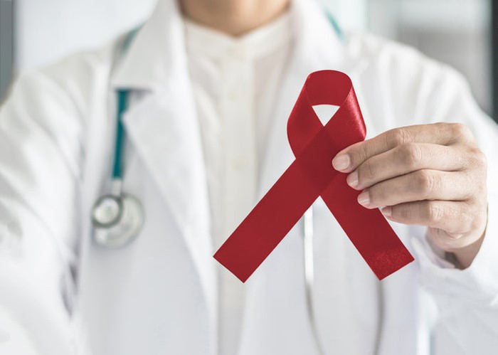 Doctor holding a burgundy ribbon.