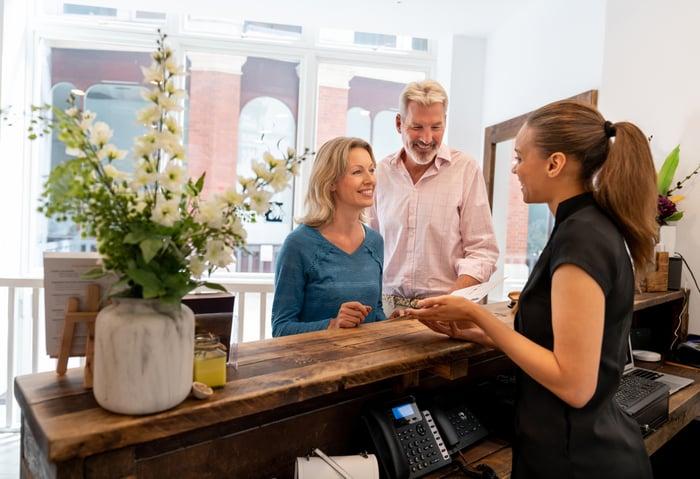 Un couple souriant parle à une femme à la réception.