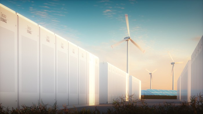 Energy storage batteries in front of a wind farm.