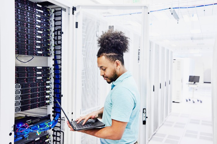 a man works on a laptop while standing next to a cabinet holding computer servers