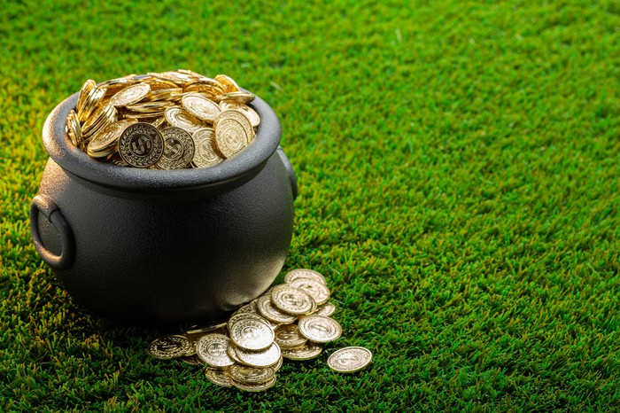 A cast-iron bucket full of gold coins on a green lawn.