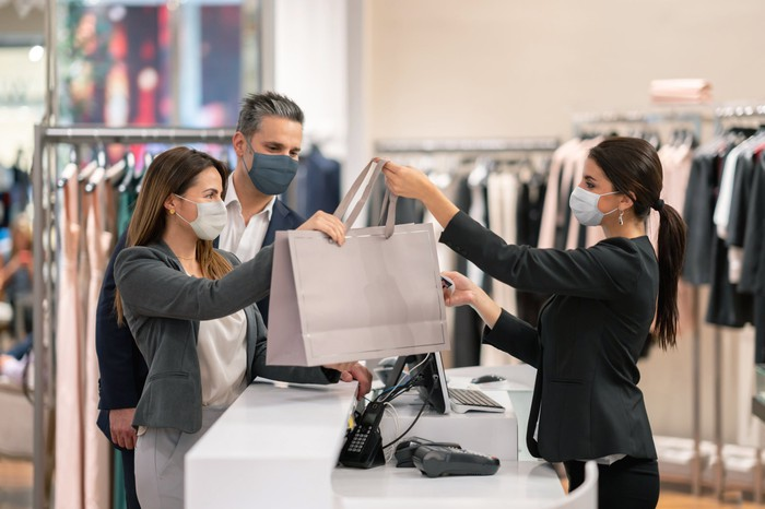 A department store worker giving two people their bag of purchased items.