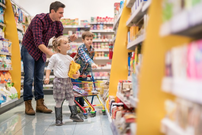 Two kids at a store with an adult.