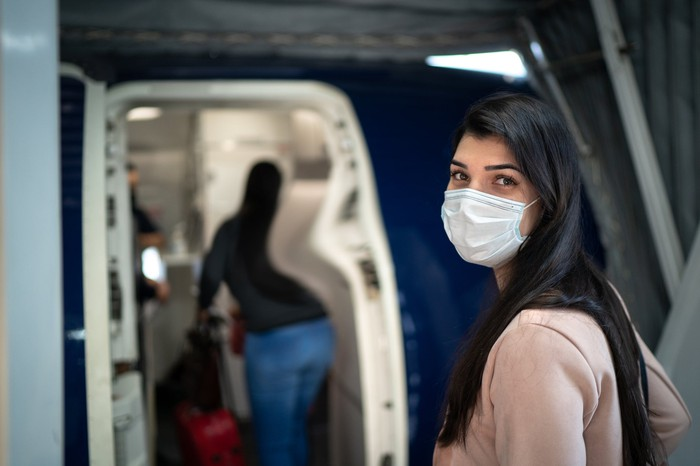 Masked person about to enter an airplane.
