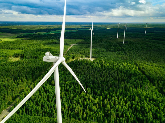 Five wind turbines in a forested area.