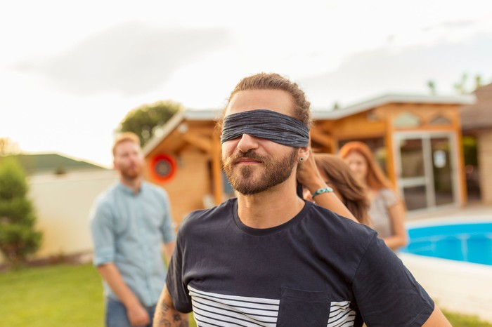 A blindfolded man at a party.