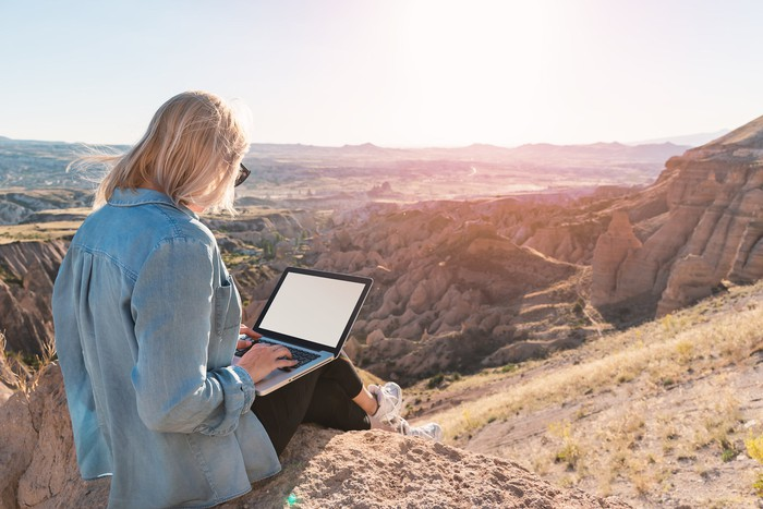 Person sitting on top of mountain using a laptop computer