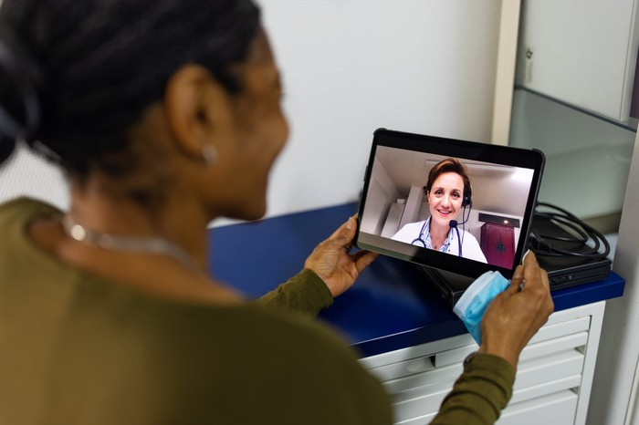 A patient having a virtual visit with a doctor through a tablet.