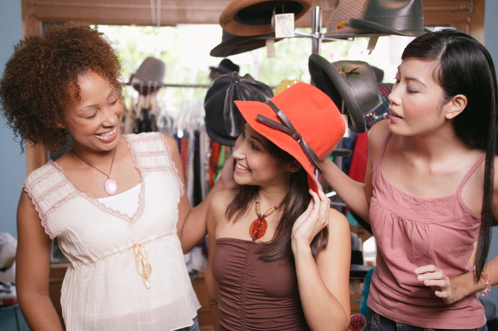 Three people trying on hats at a store.