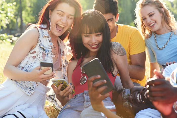 People smiling while using social media apps on their mobile phones.