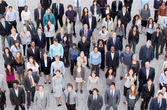 A diverse crowd of people in business formal attire.