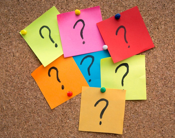 Seven square pieces of paper of various colors, with a question mark written on each, tacked to a bulletin board.