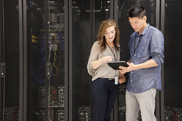 Two IT professionals check a tablet in a server room.