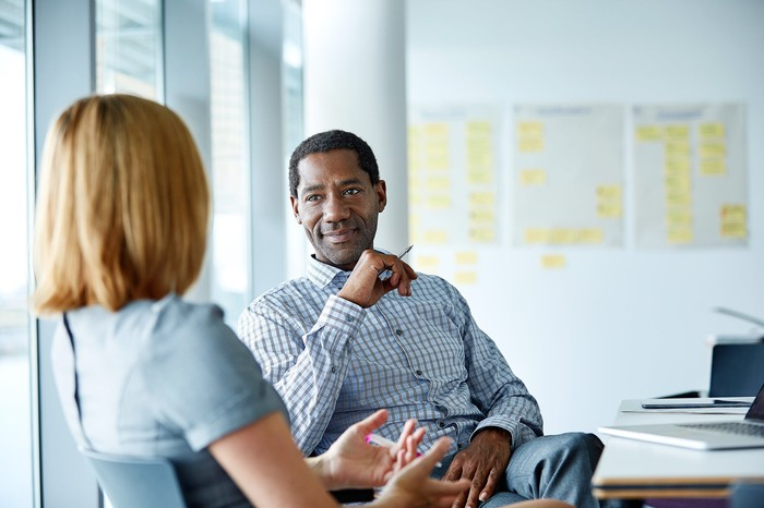 Two colleagues talking in an office.