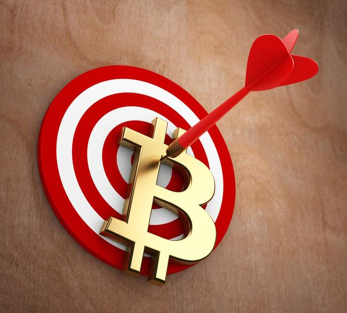 Bitcoin symbol pinned to a dartboard